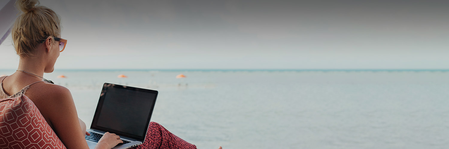 lady working on her laptop at the beach