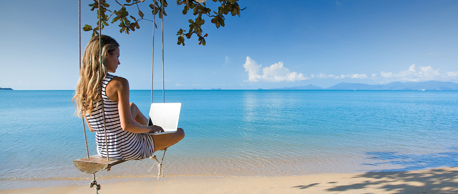 lady on her laptop while on a tree swing by the beach